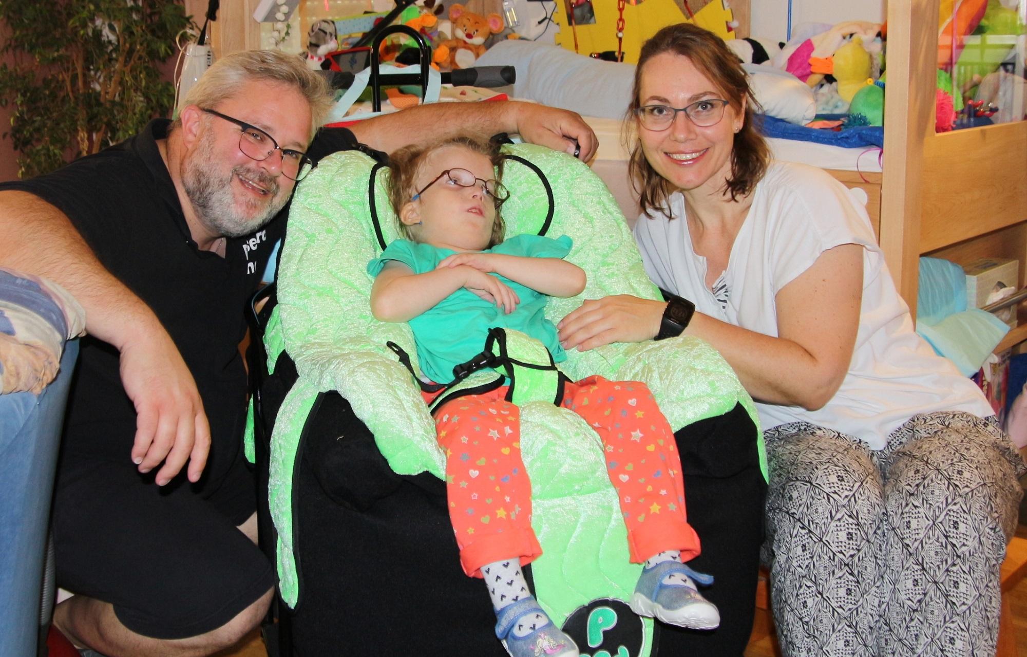 Eltern knien links und rechts neben kleinem, kranken Mädchen in Krankensitz