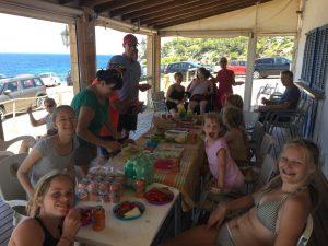 Gruppe beim gemeinsamen Essen auf einer Terrasse am Meer