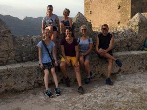 Familie sitzt auf Steintreppe vor einem Turm