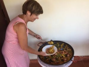 Frau, die sich Paella aus einer großen Pfanne schöpft