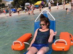Mädchen im Schwimmrollstuhl im Meer