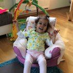 Kleines lachendes Mädchen in speziellem Sitz