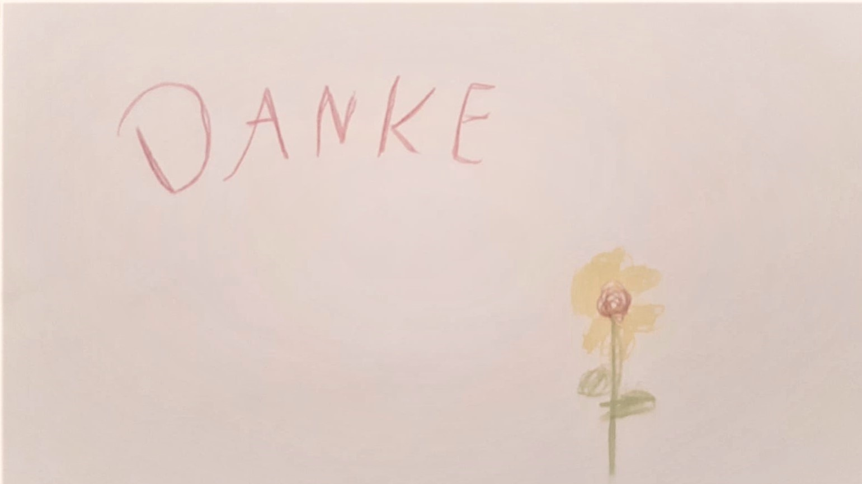 Kinderzeichnung einer gelben Blume mit dem Wort Danke in Großbuchstaben