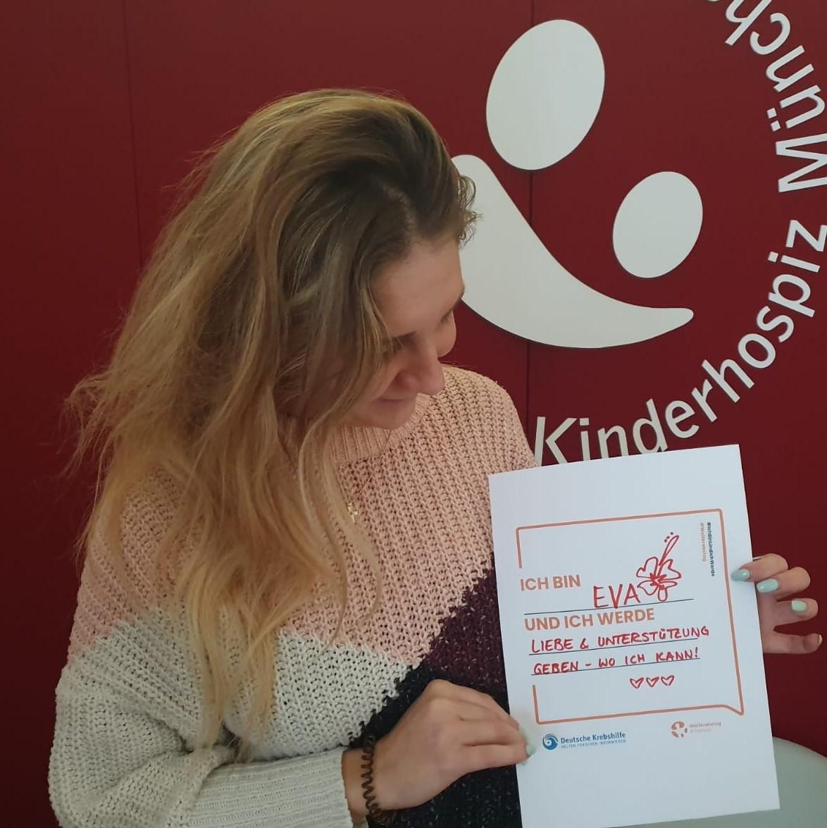 Mitarbeiterin des AKM mit Schild zum Weltkrebstag Ich bin und ich werde
