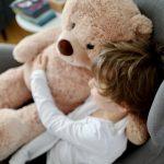 Kind umarmt Teddybär