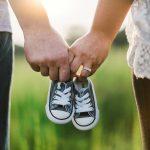 Eltern halten sich an den Händen mit Babyschuhen