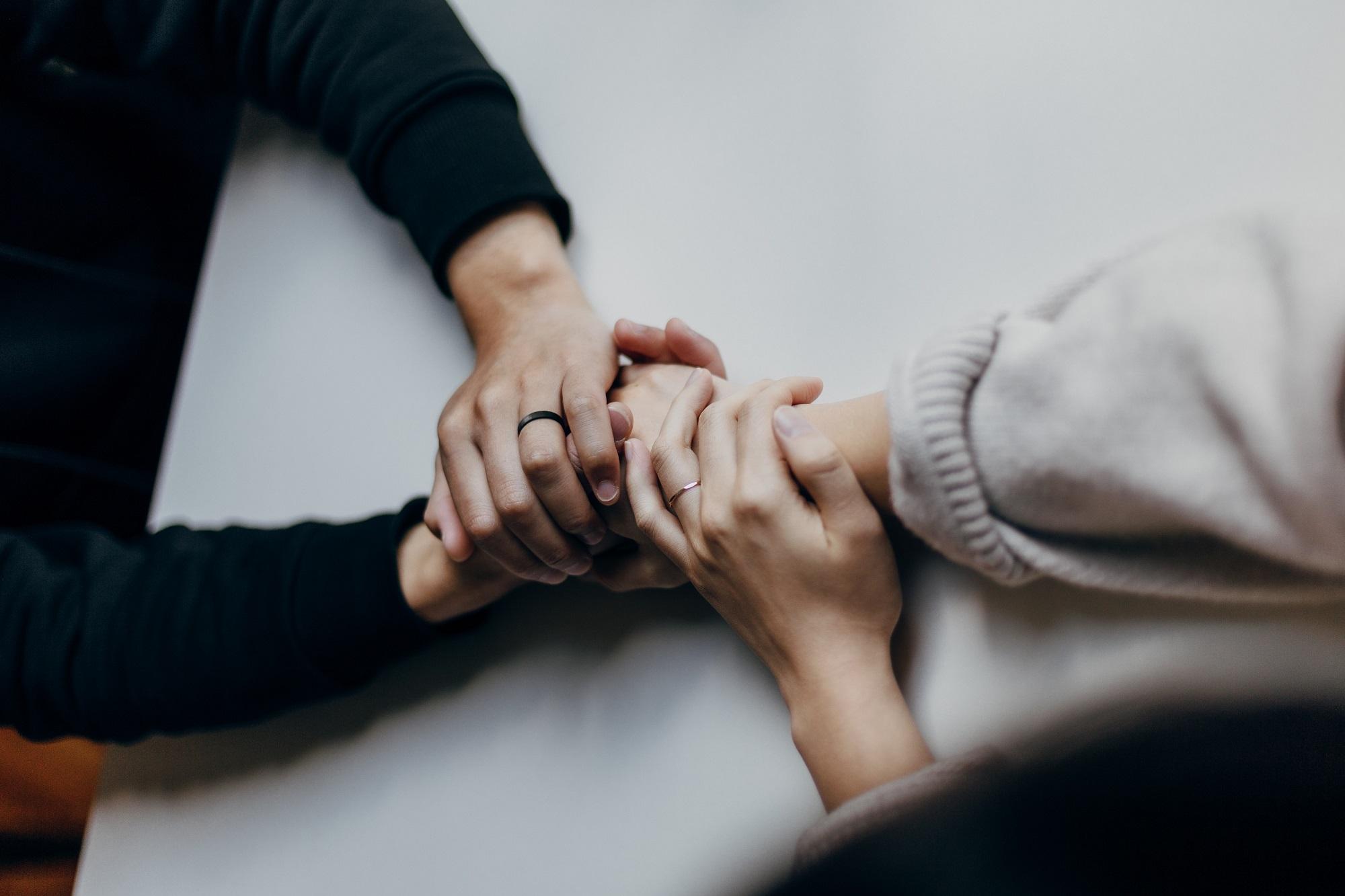 Gesprächssituation, bei der sich zwei Menschen an den Händen halten