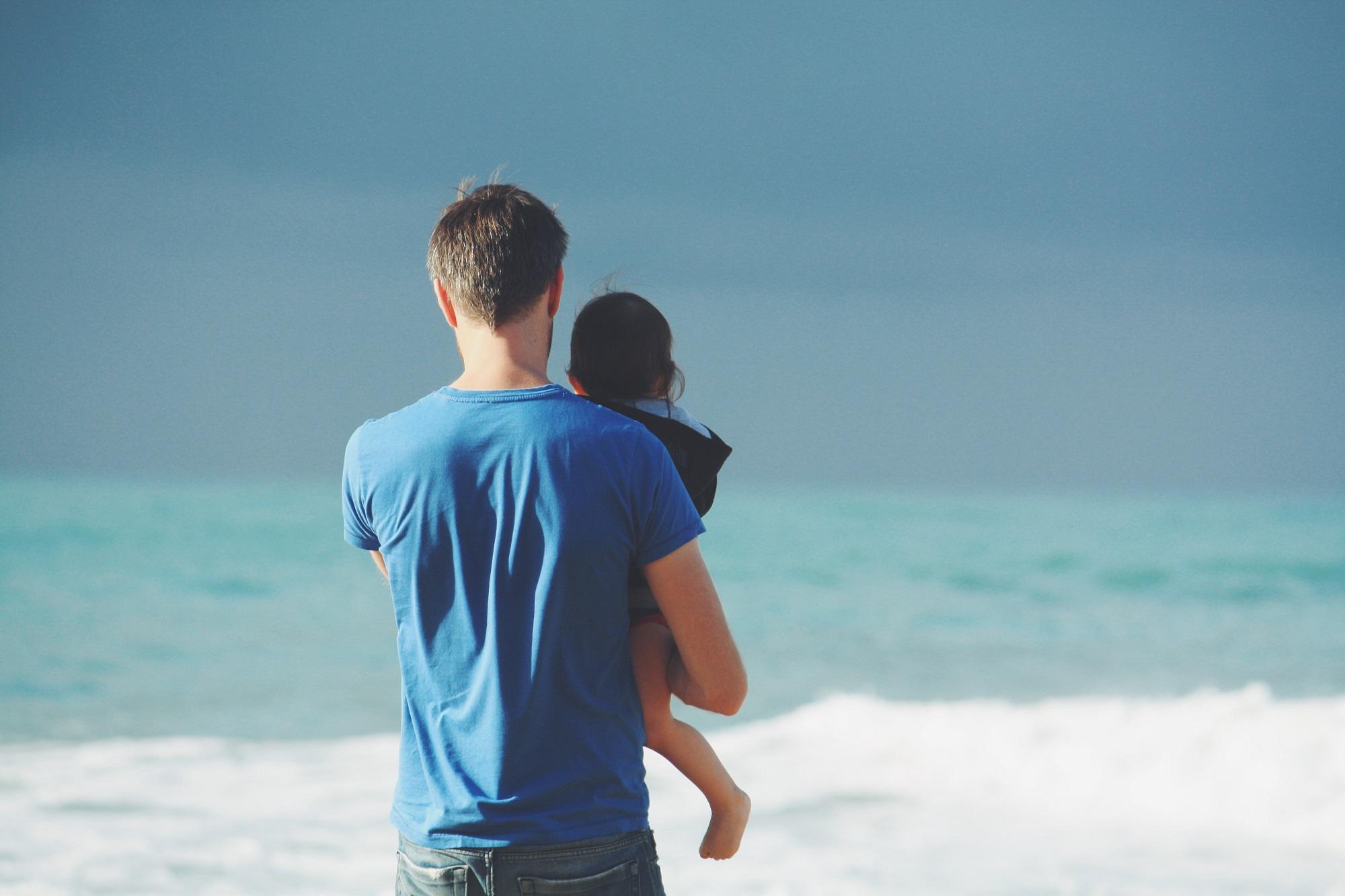 Vater mit Kind im Urlaub am Meer