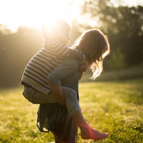 Mädchen trägt kleinen Jungen auf dem Rücken durchs Gras